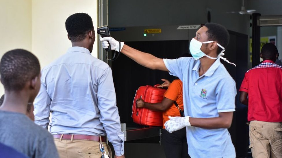 One worker dey check di temperature of travellers for di border post with Kenya for Namanga, northern Tanzania, on March 16, 2020, on di day Tanzania confam im first case of Covid-19.