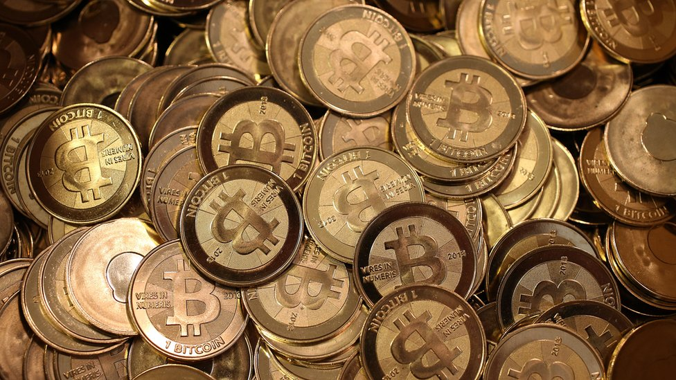 A pile of bitcoin pieces sit in a box