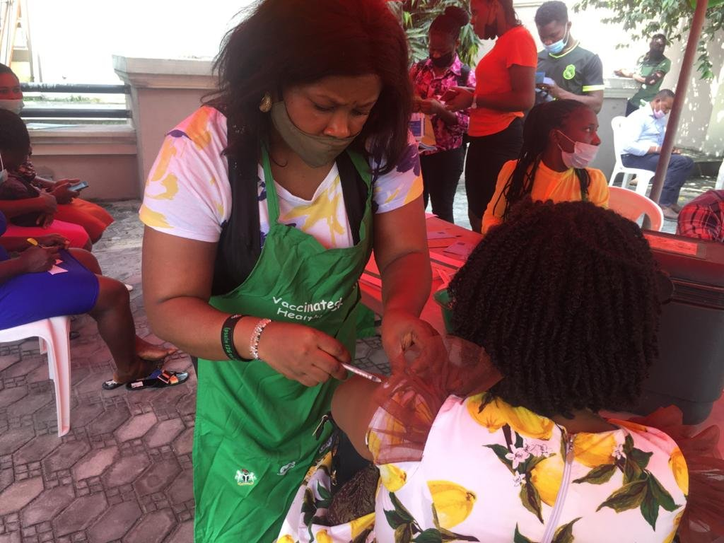 Health worker dey inject woman wit Covid-19 vaccine